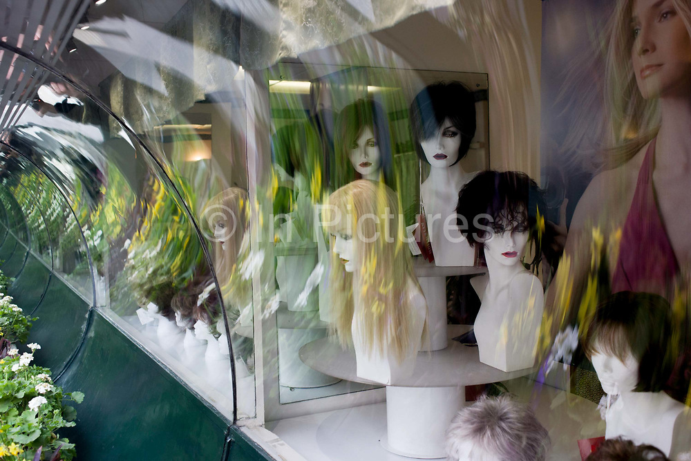 Wigs on bust models seen in the window of a retailer in central London. Reflected in a curved mirror, the mannequins' busts appear as repetitions into the distance along with outside vegetation from an exterior plant arrangement in the street. Various hair styles are seen for women to try on and buy.
