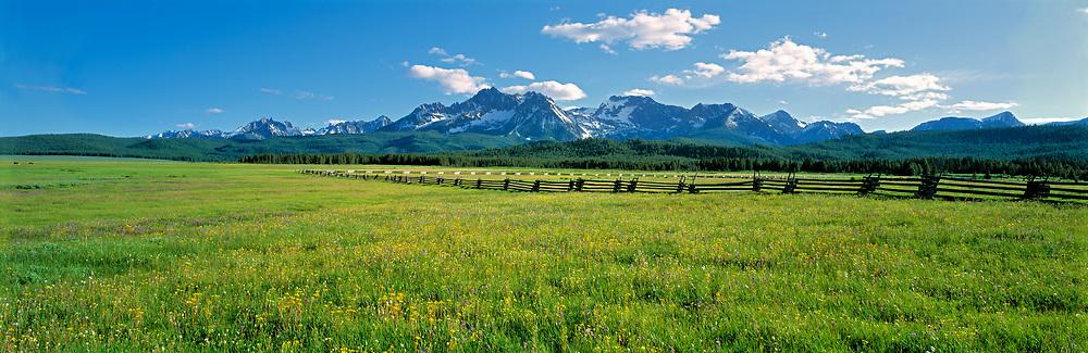 A split-rail fence extends to the Sawtooth Range at Sawtooth NRA, Idaho.