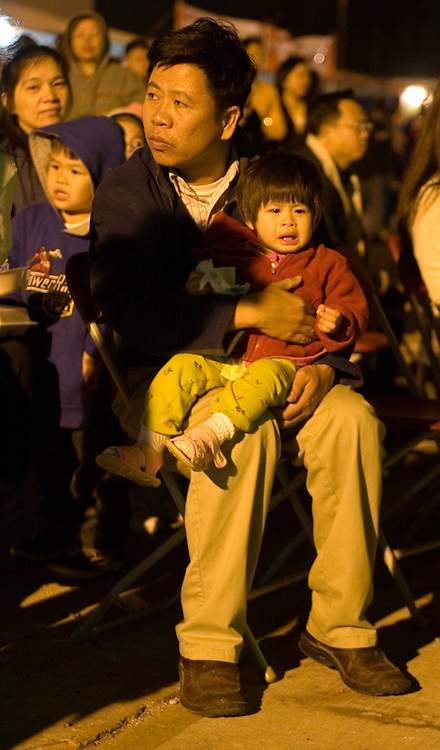 03 Feb 2006. East New Orleans, Louisiana. <br /> Tet, or Tet Nguyen Dan, Vietnamese Lunar New Year. Year of the Dog celebrations amongst the Vietnamese community of East Orleans. A father and child sit in the crowd listening to traditional Vietnamese music.<br /> Photo; Charlie Varley/varleypix.com