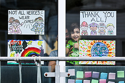 © Licensed to London News Pictures. 15/05/2020. London, UK. A boy looks out of the window next to a display of hand painted messages for NHS staff and key workers in a house in north London. Rainbows are used as a symbol of peace and hope. <br /> <br /> ***Permission Granted***<br /> <br /> Photo credit: Dinendra Haria/LNP