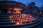 "A person places candles at  a makeshift memorial in Berlin, Germany, January 17,  2021. The memorial is part of the initiative  ""Corona-Tote sichtbar machen"" (lit. Make corona deaths visible) by Christian Y. Schmidt and Veronika Radulovic,  since December 6, 2020, people gather at the fountain of Arnswalder Platz every Sunday at 16:00, light candles and place placards with the current death toll reported in Germany at the time. The death toll in Germany by variouse sources revolved around 47,000."