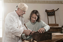 Restorer master explains apprentice something on an antique bone box, Bavaria, Germany