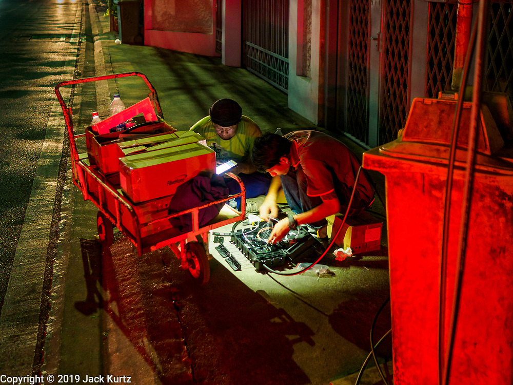 27 FEBRUARY 2019 - BANGKOK, THAILAND: Men who work for an internet service provider use a flashlight on a smart photo  while they hook up a customer's internet in a Bangkok residential neighborhood. Bangkok, a city of about 14 million, is famous for its raucous nightlife. But Bangkok's real nightlife is seen in its markets and street stalls, many of which are open through the night.       PHOTO BY JACK KURTZ