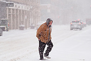 29 DECEMBER 2020 - DES MOINES, IOWA: A man crosses Locust Street in downtown Des Moines during the heaviest snowfall so far of the 2020-21 winter. Des Moines was expected to get about 8 inches of snow before Wednesday morning. Statewide, across Iowa, more than 900 snowplows have been called out to clear the roads.       PHOTO BY JACK KURTZ