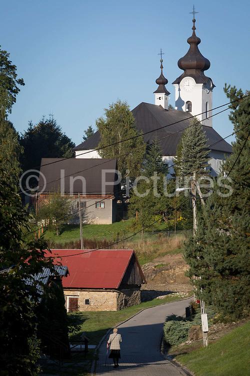 A lady worshipper walks to Sunday Mass at the Greek-Catholic Jana Chrzciciela church, on 21st September 2019, in Jaworki, near Szczawnica, Malopolska, Poland.