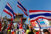 01 FEBRUARY 2014 - BANGKOK, THAILAND:  Anti-government protestors in Bangkok wave the Thai flag and block the famous Chinatown Gate during a protest. The anti-government protest movement, led by the People's Democratic Reform Committee (PDRC) organized a march through the Chinatown district of Bangkok Saturday and disrupted the city's famous Chinese New Year festival. Some streets were blocked and protest leader Suthep Thaugsuban walked through the neighborhood collecting money. The march was in advance of massive protests the PDRC has promised for Sunday, Feb. 2 in an effort to block Thais from voting in the national election.    PHOTO BY JACK KURTZ