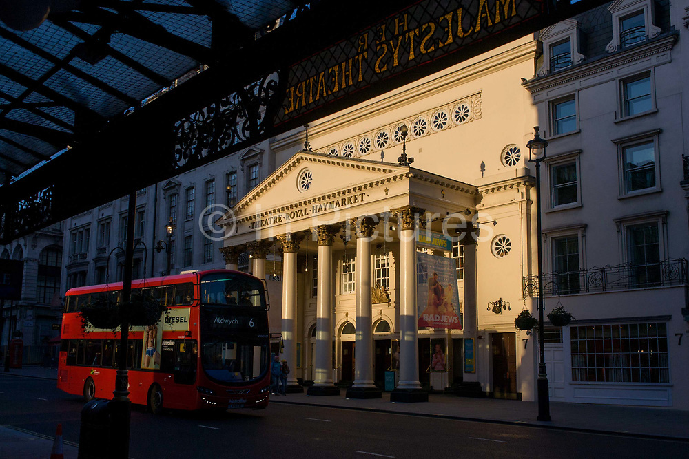 A number 6 red London bus bus drives along on a late on a winter's afternoon, passing the sunlit exterior of the Haymarket Theatre in central London. Warm light shines on the pillars and columns of this famous cultural landmark in the borough of Westminster. The Theatre Royal, Haymarket (also known as Haymarket Theatre or the Little Theatre) is a West End theatre in the Haymarket in the City of Westminster which dates back to 1720, making it the third-oldest London playhouse still in use.