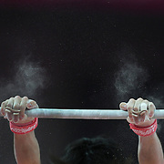 A Japanese gymnast performs his horizontal bar routine as chalk dust hangs in the air from the impact of catching the bar during the Men's Artistic Gymnastics podium training at North Greenwich Arena during the London 2012 Olympic games preparation at the London Olympics. London, UK. 25th July 2012. Photo Tim Clayton