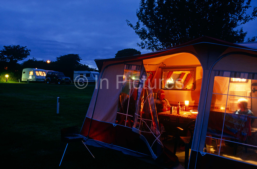 As evening light fades, campers who are relaxing in the awning of their caravan are having a sociable time with friends. Their table has drinks and an outdoor campers' light and we see through the open flap of their awning at a caravan site at Looe in Devon, England. Other vehicles can be seen in the distance, all lined up against the hedged-border of this field, run by the prestigious Caravan Club of Great Britain whose membership stands around 1 million members. Formed in 1907 the club boasts over 900 staff and an annual turnover of around £100 million. Rules about pitching vans and how to behave with waste, children and noise are strictly controlled and often, sites specialise more for families with kids or for older people wanting more peace.