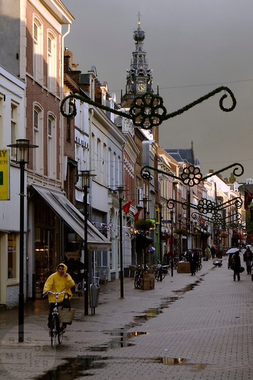 Een vrouw fietst in de regen door de binnenstad van Nijmegen waar donkere wolken zijn samen gepakt.