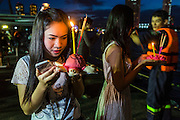 """17 NOVEMBER 2013 - BANGKOK, THAILAND: Women pray before floating their krathongs in the Chao Phraya River near Wat Yannawa in Bangkok. Loy Krathong (also written as Loi Krathong) is celebrated annually throughout Thailand and certain parts of Laos and Burma (in Shan State). The name could be translated """"Floating Crown"""" or """"Floating Decoration"""" and comes from the tradition of making buoyant decorations which are then floated on a river. Loi Krathong takes place on the evening of the full moon of the 12th month in the traditional and they do this all evening on the 12th month Thai lunar calendar. In the western calendar this usually falls in November. The candle venerates the Buddha with light, while the krathong's floating symbolizes letting go of all one's hatred, anger, and defilements       PHOTO BY JACK KURTZ"""
