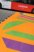 A 'Toots' London tour bus drives over the multi-coloured markings of a crossing at Piccadilly Circus, on 16th July 2021, in London, England.