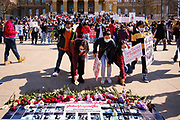 06 MARCH 2021 - DES MOINES, IOWA: Members of Iowa's Burmese community lay flowers on a memorial for people killed by the Burmese military during anti-coup protests in Myanmar. About 300 members of the Burmese community in Iowa gathered at the State Capitol in Des Moines Saturday to protest against the military coup that deposed the popularly elected government of Aung San Suu Kyi and continuing military oppression in Myanmar. There are about 10,000 people in Iowa's Burmese community.           PHOTO BY JACK KURTZ