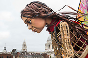 Little Amal, a giant puppet of a Syrian refugee girl fleeing conflict, gazes into the River Thames from the Millennium Bridge after being welcomed at St Pauls Cathedral on 23rd October 2021 in London, United Kingdom. The 3.5-metre puppet, which is nearing the end of an 8,000km journey from the Turkish-Syrian border to Manchester in support of refugees, climbed the steps of St Pauls Cathedral to present a wood carving of a ship at sea from St Pauls birthplace at Tarsus in Turkey to the dean.
