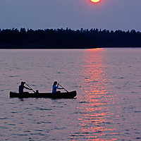 A family canoes on Lake of the Woods under a smoky sunset near Kenora, Ontario, Canada.