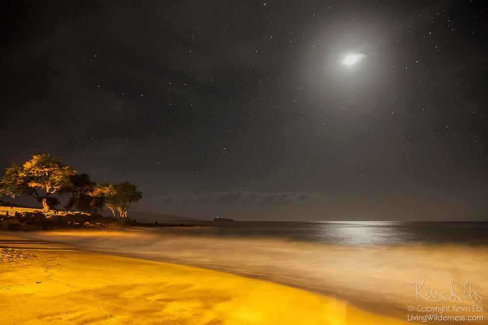 The full moon shines over Makena Beach, located on the Hawaiian island of Maui at night.