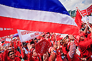 """26 MARCH 2009 -- BANGKOK, THAILAND: A Thai flag frames anti-government protestors demonstrating in favor of deposed Prime Minister Thaksin Shinawatra. More than 30,000 members of the United Front of Democracy Against Dictatorship (UDD), also known as the """"Red Shirts""""  and their supporters gathered on Sanam Luang (the vast open field in front of the Palace) and descended on central Bangkok March 26 to start a series of protests against and demand the resignation of current Thai Prime Minister Abhisit Vejjajiva and his government. The protest is a continuation of protests the Red Shirts have been holding across Thailand. Thaksin was deposed in a coup and went into exile rather than go to prison after being convicted on corruption charges. He is still enormously popular in rural Thailand.  PHOTO BY JACK KURTZ"""