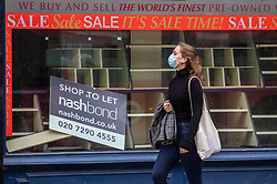 © Licensed to London News Pictures. 13/10/2020. London, UK. A women in a mask walks past an empty shop in the Strand in the West End of London. The Strand a once bustling part of Theatreland now littered with empty and boarded up shops as the Office for National Statistics figures reveal unemployment rises by a further 138,000 as fears grow many more will be on the dole by the end of the year. Yesterday Prime Minister Boris Johnson addressed the Nation to announce a new three tier lockdown system for the country as increasing levels of coronavirus infections continue to rise in the UK. Photo credit: Alex Lentati/LNP