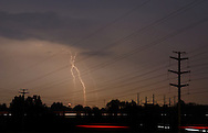 Wawayanda, N.Y. - Lightning bolts illuminate the night sky behind power lines in the Town of Wawayanda during a summer thunder storm on Aug. 7, 2006. The streaks at the bottom are car head lights and tail lights blurred during the 30-second exposure. ©Tom Bushey