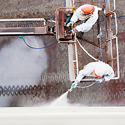 two workers spray painting