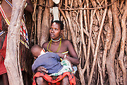 Portrait of a Datoga woman, in traditional dress and beads with deformed ear lobes, breast feeding a child. Photographed in Lake Eyasi, Tanzania
