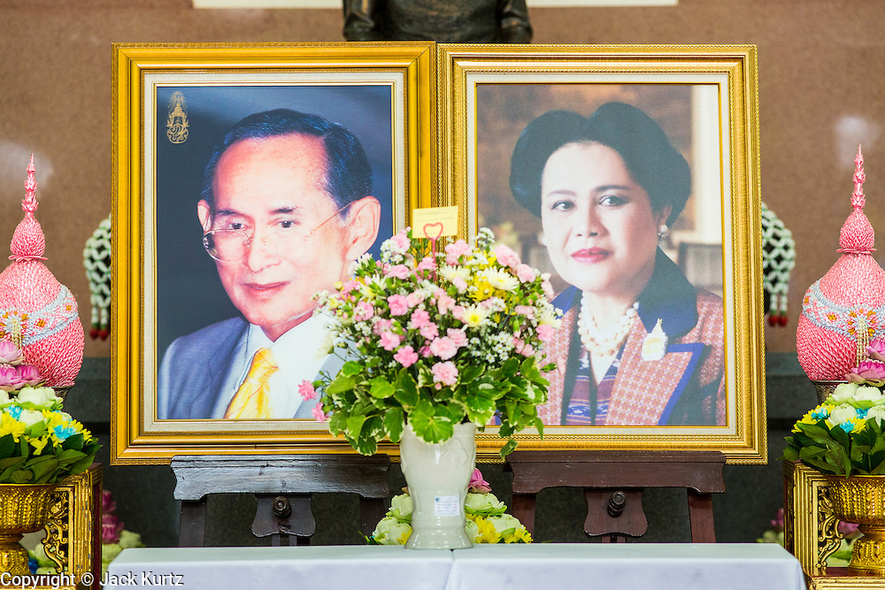 26 NOVEMBER 2012 - BANGKOK, THAILAND:    A portrait of Bhumibol Adulyadej, the King of Thailand, and his wife Queen Sirikit with gifts left for them at Siriraj Hospital in Bangkok. Siriraj was the first hospital in Thailand and was founded by King Chulalongkorn in 1888. It is named after the king's 18-month old son, Prince Siriraj Kakuttaphan, who had died from dysentery a year before the opening of the hospital. It's reported to one of the best hospitals in Thailand and has been home to Bhumibol Adulyadej, the King of Thailand, since 2009, when he was hospitalized to treat several ailments. Since his hospitalization tens of thousands of people have come to pay respects and offer get well wishes. The King's 85th birthday is on Dec 5 and crowds at the hospital are growing as his birthday approaches. The King is much revered throughout Thailand and is seen as unifying force in the politically fractured country.     PHOTO BY JACK KURTZ