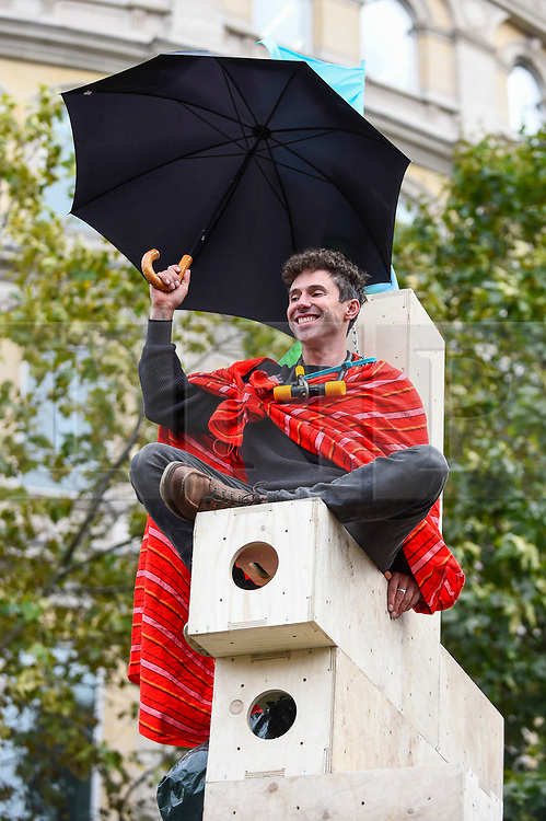 © Licensed to London News Pictures. 10/10/2019. LONDON, UK. An activist secured to the top of a wooden structure in Trafalgar Square during day 4 of Extinction Rebellion's climate change protest in the capital.  Activists are calling on the Government to take immediate action against the negative impact of climate change.  Photo credit: Stephen Chung/LNP