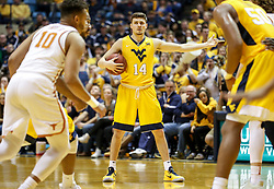Jan 20, 2018; Morgantown, WV, USA; West Virginia Mountaineers guard Chase Harler (14) looks to pass during the second half against the Texas Longhorns at WVU Coliseum. Mandatory Credit: Ben Queen-USA TODAY Sports