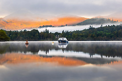 © Licensed to London News Pictures. 15/09/2021. Keswick UK. The mountains that surround Derwent Water in Keswick, Cumbria, glow orange as the mist clears & the sun rises in the Lake District this morning. Photo credit: Andrew McCaren/LNP