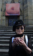 Yoko Ono shines a 'love torch' at a photocall on the steps of St Luke's Cathedral under one of her controversial images which she has donated to the 3rd Liverpool Biennial, the UK's largest contemporary arts event which commences on September 18, 2004 and runs until November 28. The image is being used to promote the Biennial..