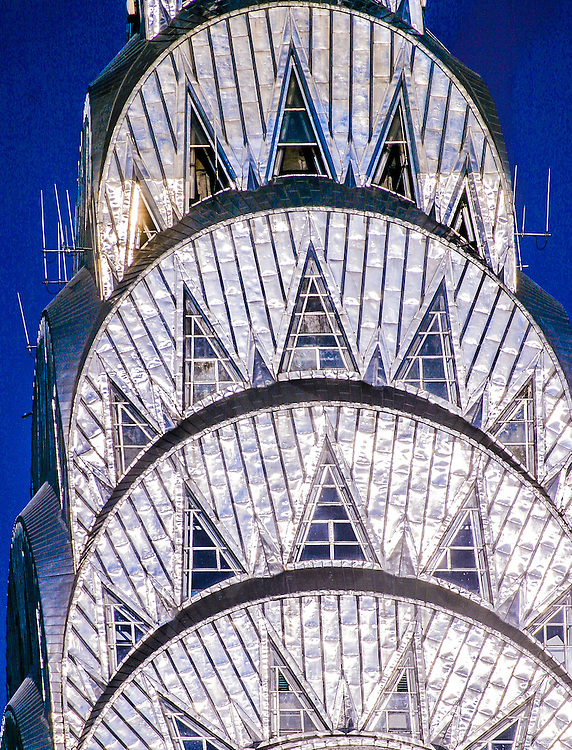 Super close-up details of the Chrysler Building's Art Deco crown with sunshine glinting off the stainless steel panels