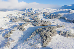 Glen Coe, Scotland, UK. 3 December 2020. A cold front has brought the first snowfall to the Scottish Highlands. Rannoch Moor and Glen Coe are covered in several inches of snow. Bright sunshine throughout the day created beautiful winter landscapes.  Pictured; Aerial view of A82 passing over snow covered Ranch Moor.  Iain Masterton/Alamy Live News