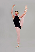 Female blond Ballet Dancer balances on on one foot