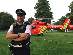 © Licensed to London News Pictures. 21/07/2021. London, UK. A police officer stands guard as the air ambulance lands in Max Roache Park near to a fatal stabbing in Brixton, south London. An investigation is underway after a man died following a stabbing in Brixton. Police were called at 20:18hrs on Wednesday, 21 July to reports of an assault close to Brixton Underground Station. Officers attended and found a man, believed to be aged in his early 20s, suffering from a stab injury. They immediately provided first aid. The London Ambulance Service and London's Air Ambulance also attended but despite their efforts the man was pronounced dead at the scene at the 20:45hrs. His next of kin has been informed and are being supported by officers. Formal identification has not taken place. A man was arrested nearby on suspicion of causing grievous bodily harm. Photo credit: Andy Gatt/LNP