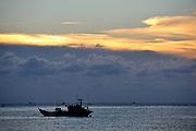 Fishing boat silhouetted against the setting sun, Hang Dua Bay, Bai Truoc (Front Beach or Tam Duong), Vung Tau, Vietnam