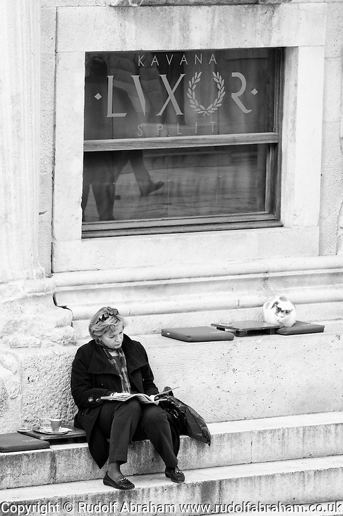 Woman and cat outside Kavana Luxor (Cafe Luxor), on the Peristil in Diocletian's Palace, Split, Croatia