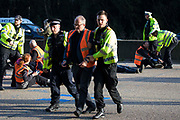 Surrey Police officers remove Insulate Britain climate activists from the clockwise carriageway of the M25 between Junctions 9 and 10 where they had been protesting as part of a campaign intended to push the UK government to make significant legislative change to start lowering emissions on 21st September 2021 in Ockham, United Kingdom. Both carriageways were briefly blocked before being cleared by Surrey Police. The activists are demanding that the government immediately promises both to fully fund and ensure the insulation of all social housing in Britain by 2025 and to produce within four months a legally binding national plan to fully fund and ensure the full low-energy and low-carbon whole-house retrofit, with no externalised costs, of all homes in Britain by 2030.