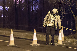 © Licensed to London News Pictures . 02/12/2012 . Bury , UK . A police officer arranges cones to block the road . Scene of a fatal road traffic accident on Bury Road , Radcliffe . Police report a car , a silver VW Polo , overturned and collided with a tree after it was observed driving at excess speed along Bury Road . A police car with its emergency equipment activated was in pursuit at the time . The driver and a passenger died at the scene . The road is closed . Photo credit : Joel Goodman/LNP