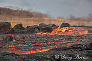 lava erupting from fissure 8 ( Puka Ewalu ) of the Kilauea Volcano east rift zone in Leilani Estates subdivision, near Pahoa, flows downslope as a glowing river of hot lava through lower Puna to enter the ocean at Kapoho, Puna District, Hawaii Island ( the Big Island ), Hawaiian Islands, U.S.A.; heat waves rising from the lava shimmer the air, distorting the view of everything beyond the edge of the river