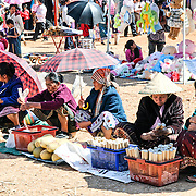 Vendors sell their wares at the New Year celebration in Phonsavan. Young Hmong men and women flock to the New Year festival in in Phonsavan in northeastern Laos. Hmong girls dress in brightly colored costumes and engage ball games of catch as part of a ritual traditionally designed to find husbands. The people of the region are predominantly of Hmong ethnicity.