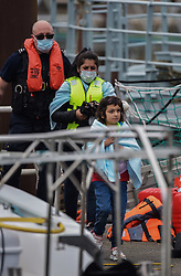 © Licensed to London News Pictures. 12/08/2021. Dover, UK. Migrants arrive ashore from a Border Force vessel at Dover Harbour in Kent after crossing the English Channel today. Hundreds of migrants have made the crossing in recent weeks. Photo credit: Stuart Brock/LNP