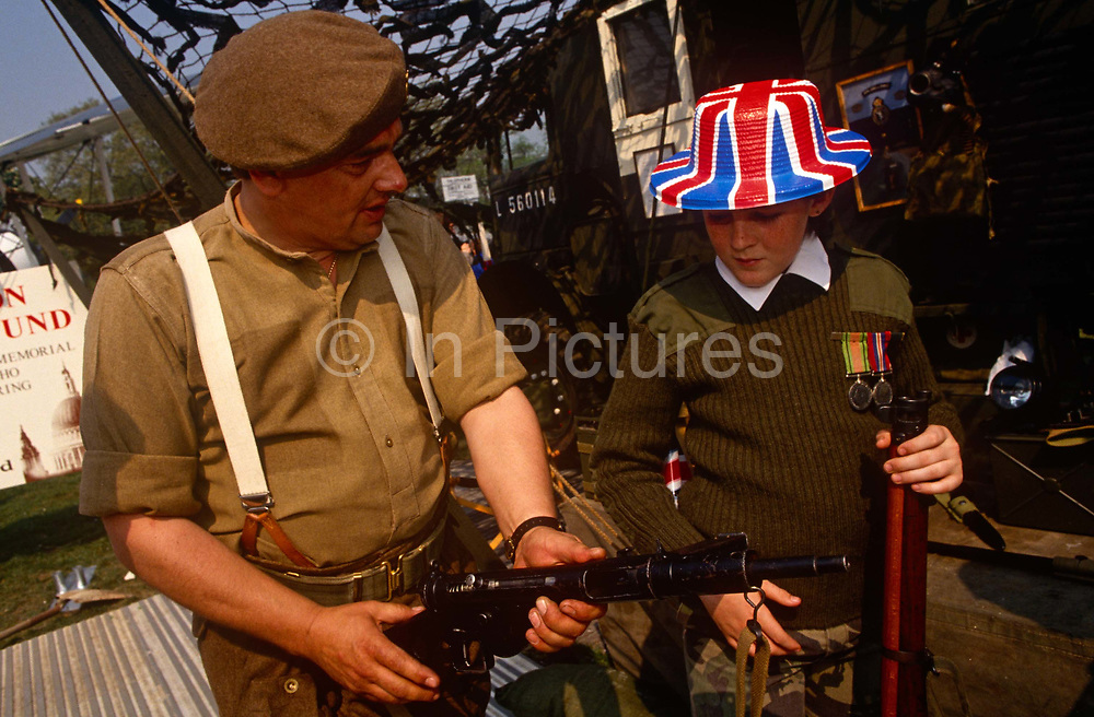 While crowds wave Union Jack flags a re-enactment soldier shows a youngster wearing a WW2 costume how to use a Thompson sub-machine gun - remembering the 50th anniversary of VE (Victory in Europe) Day on 6th May 1995. In the week near the anniversary date of May 8, 1945, when the World War II Allies formally accepted the unconditional surrender of the armed forces of Germany and peace was announced to tumultuous crowds across European cities, the British still go out of their way to honour those sacrificed and the realisation that peace was once again achieved. Street parties now – as they did in 1945 – played a large part in the country's patriotic well-being.