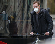 A man wearing protective face mask cycles across central London in Westminster, London, as the death toll from coronavirus in the UK reached 71 people.  Wednesday, March 18, 2020. (Photo/Vudi Xhymshiti)
