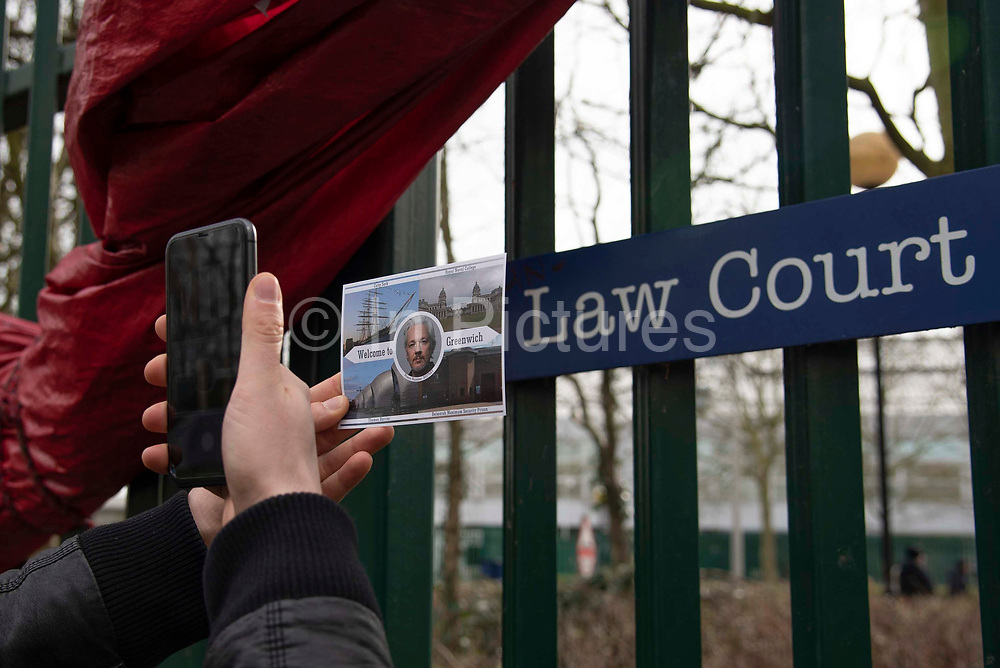 A man photographs a Julian Assange postcard with Welcome to Greenwich written across the front, outside Woolwich Crown Court during his extradition hearing on 25th February 2020 in London, United Kingdom. Wikileaks founder Julian Assange is wanted in the United States to face charges of attempted hacking and breaches of the espionage act, related to the publication of classified US military documents. He faces a maximum of 175 years in prison.