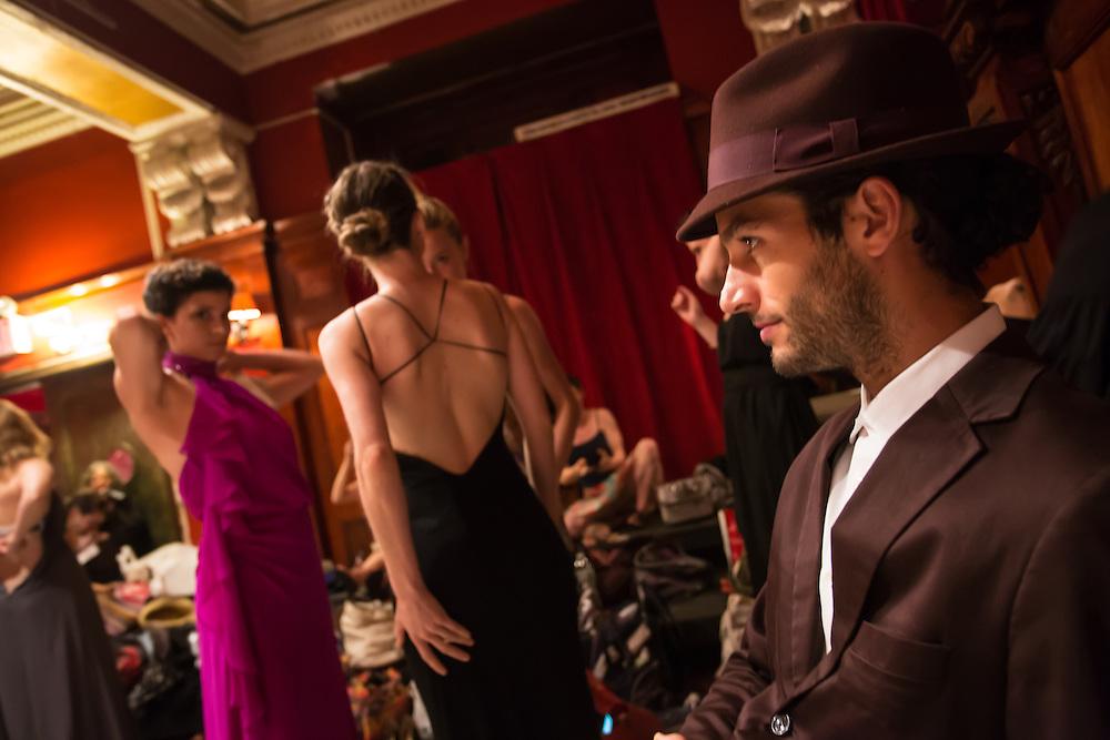A male dancer waits while women get ready.