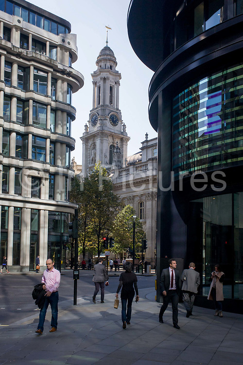 As lunchtime City workers pass-by on the street corner we see the spire of Royal Exchange - the tall structure in the gap between modern offices on Threadneedle Street in the heart of the capital's financial district known as The Square Mile. The Royal Exchange in London was founded in the 16th century by the merchant Thomas Gresham to act as a centre of commerce for the City of London. Its design was inspired by a bourse Gresham had seen in Antwerp, and was Britain's first specialist commercial building. It has twice been destroyed by fire and subsequently rebuilt. The present building was designed by William Tite in the 1840s. The site was notably occupied by the Lloyd's insurance market for nearly 150 years. Today the Royal Exchange contains offices, luxury shops and restaurants.