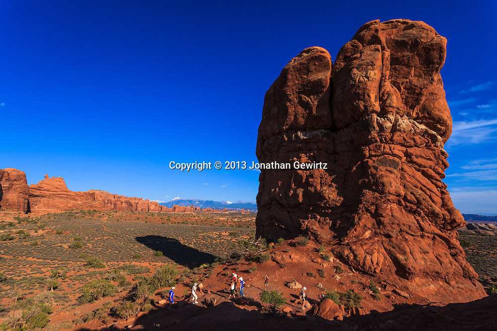 Visitors to Balanced Rock in Arches National Park, Utah. WATERMARKS WILL NOT APPEAR ON PRINTS OR LICENSED IMAGES.
