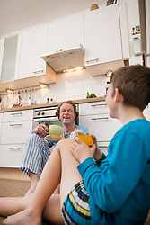 Happy father and son sitting on floor in kitchen
