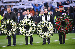 Aiyawatt Srivaddhanaprabha (second right) lays a wreath for Armistice Day and those who lost their lives in the Leicester City helicopter crash including Leicester City chairman Vichai Srivaddhanaprabha ahead of the Premier League match at the King Power Stadium, Leicester.