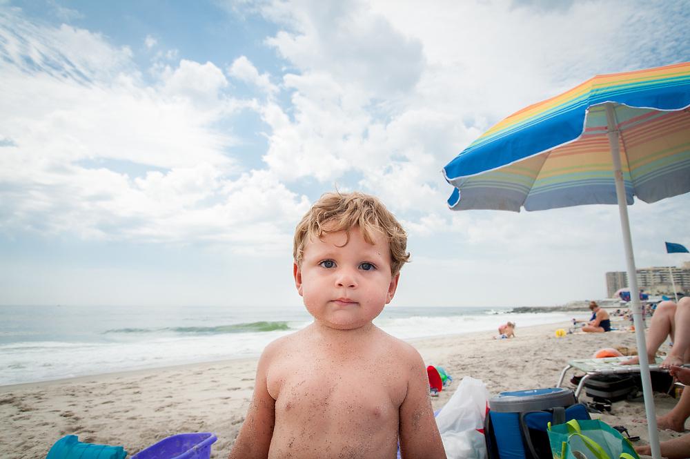 Boy at the beach with umbrella.
